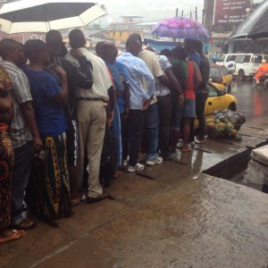 QUEUING IN PAIN … commuters stand-in-line under the rain at the Lumley bus stop, waiting for government buses
