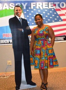 Asmaa poses with a portrait image of President Obama at the US Embassy in Sierra Leone